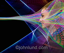 Futuristic communications are illustrated in this dynamic and colorful stock photo showing a woman engulfed in complex light patterns of energy and streaming data.