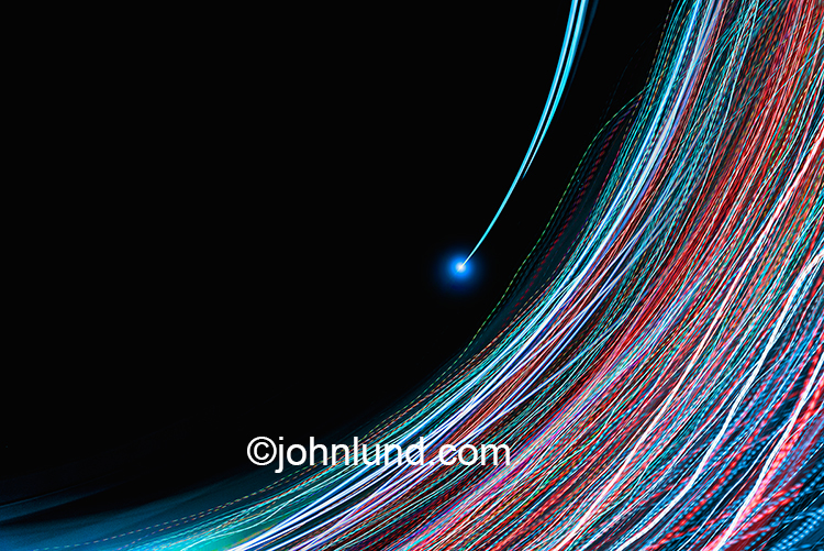 "Future digital communications are illustrated in this stock photo featuring multi-colored light trails arcing across the frame against a black background with one light trail having a blue glow at it""s tip."