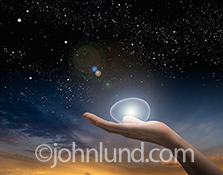 The future, the way forward, and innovation are all powerfully illustrated in this concept stock photo showing a translucent egg resting on the palm of a woman's hand against a star filled dawn sky.