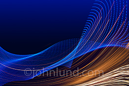 Streaming data is beautifully illustrated in this big data stock photo featuring blue and gold light trails creating patterns as they flow gracefully across a blue-to-black gradated background.