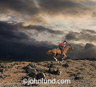 Storm clouds gather over the head of a cowboy galloping his horse over rough terrain in an image about challenge, change, skill and speed.