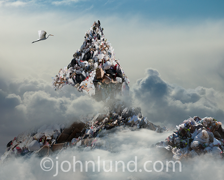 A towering mountain of garbage rises up through the clouds as an egret flies by in the foreground in an image for illustrating environmental issues.