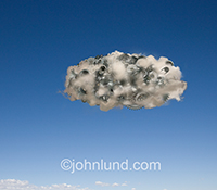 The infrastructure of cloud computing is metaphorically illustrated in this stock photo showing a single cloud, filled with gears and cogs, against a blue sky. This is an image about the inner workings of online computing.