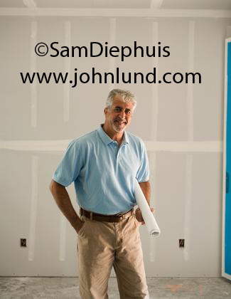 Portrait of a general contractor holding a rolled up set of blue prints under his arm and smiling at the camera. Small businessman making good.  Contractor standing in un-painted new home.