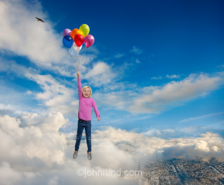 A young girl floats happily through the sky and over the clouds clutching a cluster of balloons in a stock photo about fantasy, adventure and possibilities.