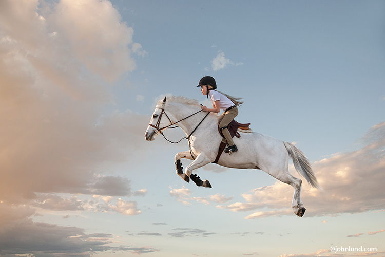 A girl sits astride a white horse leaping high into the air over an unseen obstacle in an image about courage, daring, and accomplishment.