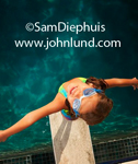 A young pre-teen girl wearing swim goggles is standing on the end of a diving board and she has her arms outstretched as she looks straight up above her at the camera.