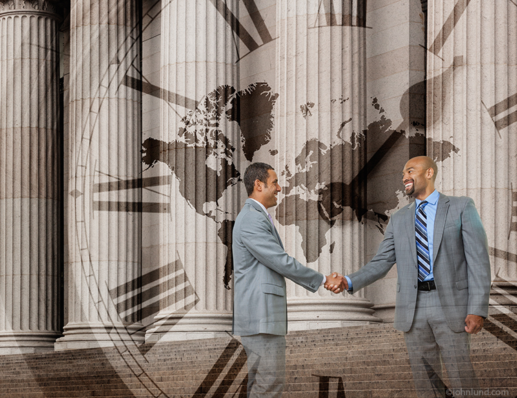 Two business executives shake hands against a backdrop of a wall street scene with a global map and clock face superimposed in a metaphor for timely global agreements and teamwork.