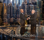 A global business agreement has just been completed with a handshake in this photo of two executives shaking hands in a symbolic global metropolis.