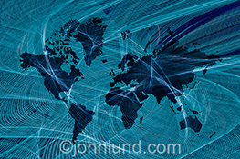 Global communications technology is visually represented in this image of a map of the continents enveloped in a complex pattern of streaking blue lights in a stock photo about the future, communications, and global connections.