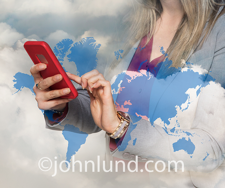 Global cell phone use is seen in this photomontage stock photo close up of a woman using a cell phone combined with a cloudscape and map of the continents.