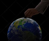 Global savings and investment are seen in this stock photo of a hand depositing a coin into the planet earth.