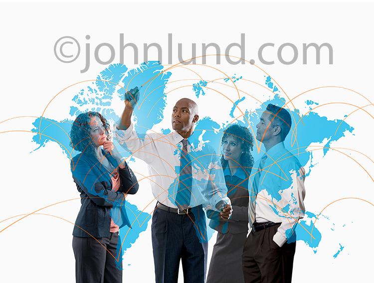 Global strategy is being mapped out in this business meeting stock photo featuring a map of the continents with connections being drawn by a senior executive in consultation with his colleagues.