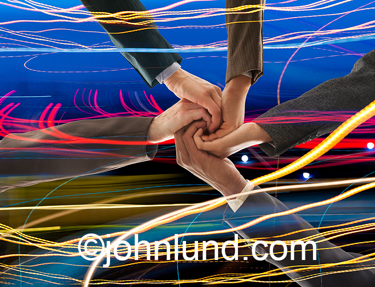 Global teamwork, connections, big data and data management are all illustrated in this colorful and dynamic stock photo that shows the hands of business executives coming together amid streaking lines of colored lights.