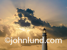 This beautiful lighthouse photo features a keeper gazing out at a sunset featuring powerful God Rays in an image about vision, guidance, the future and spirituality.