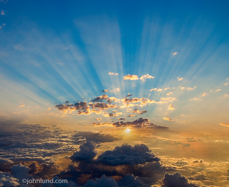 God ray clouds herald a golden sunrise in a high altitude scene that can be a metaphor for cloud computing, opportunity, spirituality and possibilities for the future.
