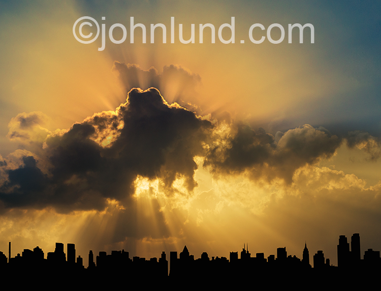 God rays burst from behind clouds over a silhouette of New York in this stock photo about possibility, opportunity and even spiritual issues.
