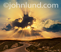 Golden god rays burst through the clouds over a winding road in an image about hope, spirituality, new beginnings and success as well as the way forward into a better future.