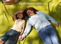 Picture of a happy young girl and her grandmother laying on their backs on a green picnic blanket laughing and holding hands. Fun family picnic pictures for advertising. Mexican families on picnics.