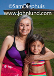 Portrait of a senior woman with her granddaughter. The woman has her arm around her grand daughter and she has long gray hair. Both are smiling and wearing bathing suits.