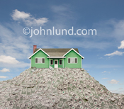 Photo of a green home sitting on top of a huge pile of money in the form of a mountain of dollars.