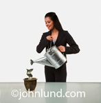 Attractive hispanic woman using a shiny metal watering can to water a dollar bill growing in a pot.  The woman is smiling, has long hair and is wearing a brown suit. Growing money.