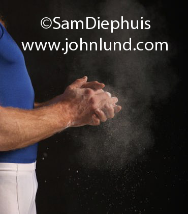 A strong muscular athlete, a gymnast, is putting chalk on his hands. A small cloud of chalk dust surrounds his hands. He is wearing a blue and white uniform.