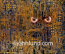 A hacker in the network is illustrated with this stock photo of a pair of evil eyes peering out from within a complex network of computer circuits.