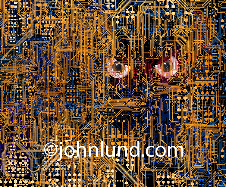 A pair of evil eyes peer out from inside complex computer circuitry in a stock photo about the dangers of artificial intelligence, hackers and cybercrime.