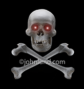 This skull and crossbones with glowing eyes on a black background is a stock photo about evil, danger and risk.