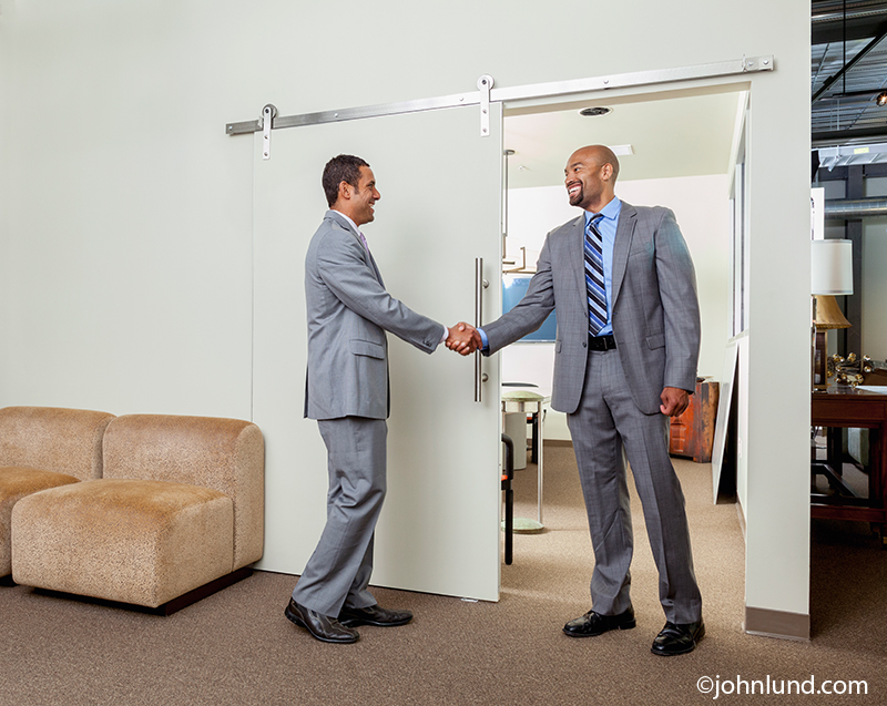 Two men clasp each other's hands in a handshake taking place in a hallway outside of a meeting room in an image about sealing the deal, teamwork and agreement.