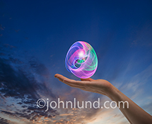 In an innovation stock photo an egg shaped orb of light trails hover over an outstretched hand.