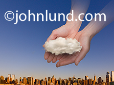 A pair of hands cup a solitary cloud over the skyline of New York in this stock photo about cloud computing and online service.