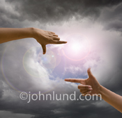 In this cloud computing photograph a pair of hands frame a break in the overcast skies that allow the sun to shine through.