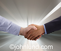 The hands of two businessmen clasp in a handshake against a background of zooming light in a stock photo about fast business, quick agreements, and speedy success in the new high tech, connected world of business.