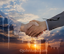 This is an unusual and beauftiful handshake photo that places the clasping hands over a city illumiated by a sunrise and with a lone jet rising above the urban skyline and the handshake.