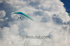 A hang glider navigates through the clouds in an image depicting freedom, getting away from it all and even exploring cloud computing.
