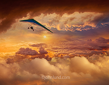 Has there ever been a more dramatic photo of a hang glider at sunset? In this stock photo a hang glider is piloting his craft in the midst of a high altitude sunset with brilliant orange hues in an image about daring, courage, freedom and unrestrained bea
