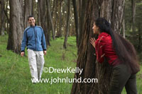 Pictures of Hid and Seek. This boyfrend, girlfriend couple is having fun playing hide and seek deep in a forest of trees.  Thick lush grass carpets the ground around the hundreds of trees.  The beautiful hispanic girlfriend is hidng.