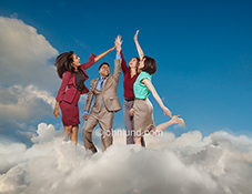 Teamwork and success in the cloud are illustrated in this stock photo featuring four businesspeople celebrating with a high-five in a cloudscape.