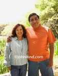 Middle aged or senior Mexican Couple posing for portrait outdoors. Heavy set Mexican man with his arm around his smiling wife. Pics of senior hispanic or Mexican people.