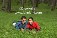 Romantic picture of a happy young couple in love laying in a field of lush green clover with a forest of trees behind them. Lifestyle picture of a couple laying in a medow facing the camera and smiling. Mexican couple in a green field of clover.