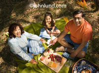 Picture of a Hispanic or Mexican family outing. Mexican family having a picnic outdoors. A hispanic family of three, mother, father, and young female child sitting on a blanket having a picnic.