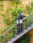 Picture of a businessman with a laptop under his arm climbing a set of metal stairs running up the side of a building covered with ivy.