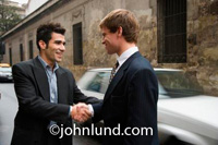 Business handshake between two men standing on the street with cars whizzing by behind them. Old weather european type buildings for the background.