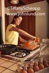 Picture of a woman in her kitchen cooking a healthy breakfast. The attractive housewife is squeezing an orange for fresh orange juice. In the foreground is an open carton of brown eggs. Frying pan, cutting board and stove top.