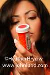 Beautiful Hispanic woman examining the label of a bottle of perscription medication. Picture of woman reading a pill bottle lable for safety information. Picture related to perscription drug abuse.