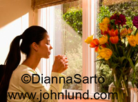 Beautiful woman drinking her coffee in the morning at home next to a large window.  Her eyes are closed and her coffee is in her hands near her mouth. Fresh pretty garden flower bouquet on the right.