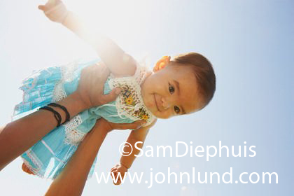 A woman's arms are shown holding a young baby girl up in the air.  The baby has short brown hair and is wearing a blue and white dress with lace.  Bright sun behind the baby and the sky is clear and blue.