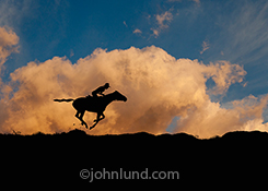 A rider and horse gallop across the prarie, silhouetted against clouds, colored a vivid orange by the setting sun, in an image about speed, freedom and journeys.